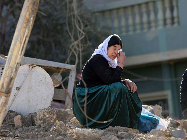 An Iraqi woman from the Yazidi community cries at her house, which was  badly damaged by Islamic State fighters, during their occupation of  Bashiqa, ...